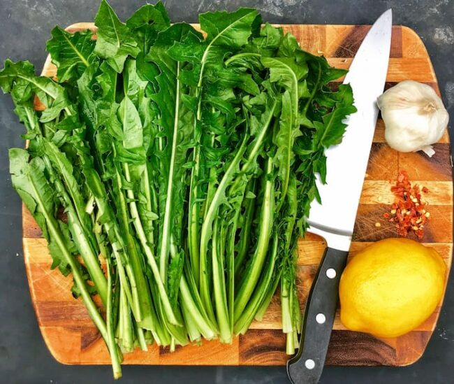 a wooden plate with the ingredients for dandelion greens and a knife