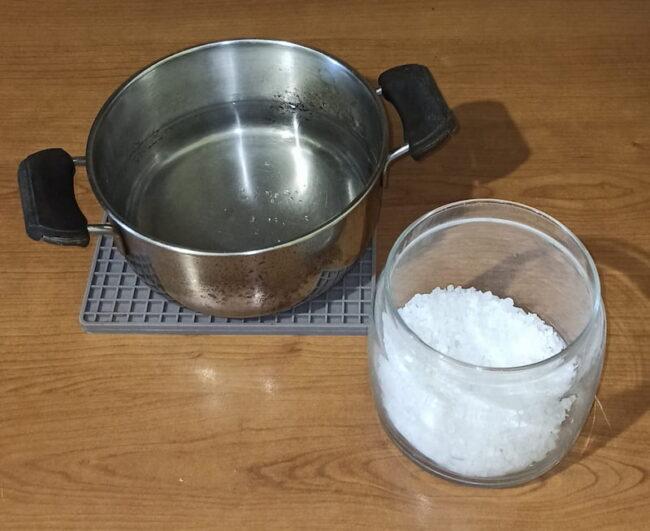 a pot of boiling water near a bowl full of salt